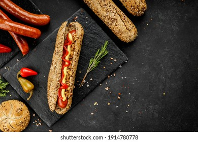 Flat lay composition of delicious hot dogs and sandwiches with different toppings on the dark background