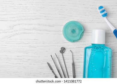 Flat lay composition with dentist tools and teeth care objects on wooden background. Space for text