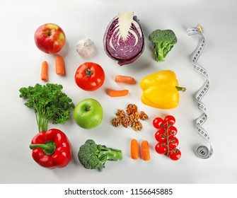 Flat lay composition with diet food and measuring tape on white background