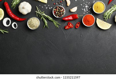Flat lay composition with different aromatic spices and space for text on dark background