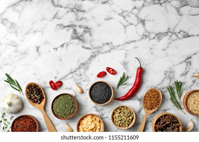 Flat lay composition with different aromatic spices and space for text on marble background