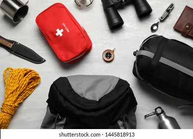 Flat lay composition with different camping equipment on light background
