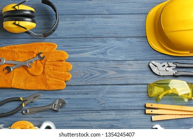 Flat lay composition with different construction tools and space for text on color wooden background