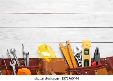 Flat lay composition with different construction tools and space for text on white wooden background