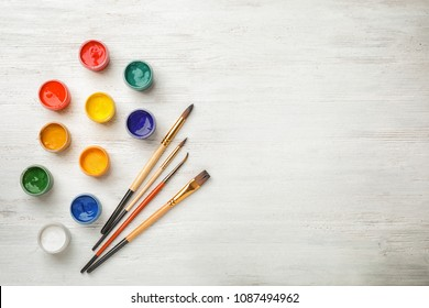 Flat lay composition with different paints and brushes on wooden background. Color palette