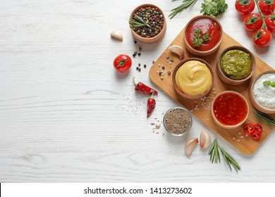 Flat lay composition with different sauces and space for text on white wooden background