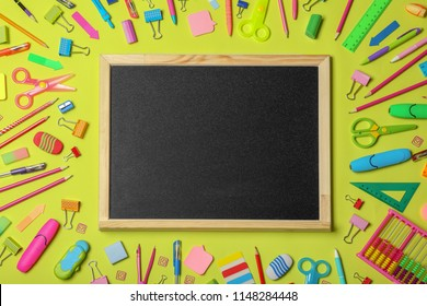 Flat lay composition with different school stationery and small chalkboard on color background