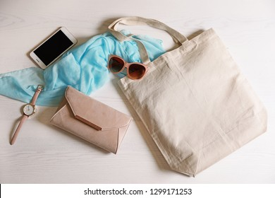 Flat lay composition with eco tote bag, smartphone and accessories on white wooden background. Space for design