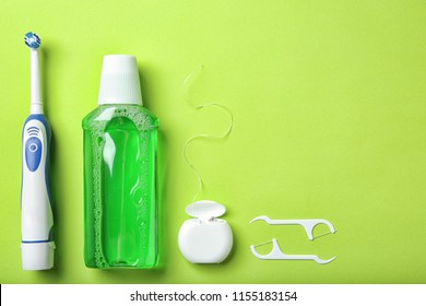 Flat lay composition with electric toothbrush and oral hygiene products on color background
