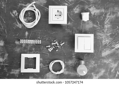 Flat lay composition with electrical outlet, switch and light bulb on grey background