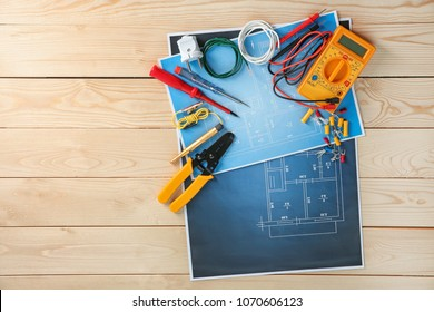 flat lay composition with electrical tools and house plan on wooden  background