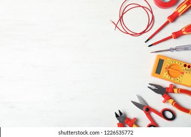 Flat lay composition with electrician's tools and space for text on wooden background