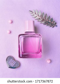 Flat lay composition with elegant perfume on light pink or violet background. Top view