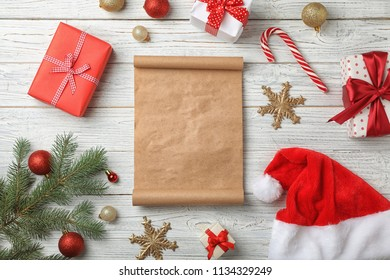 Flat lay composition with empty Santa's list and Christmas decoration on wooden background