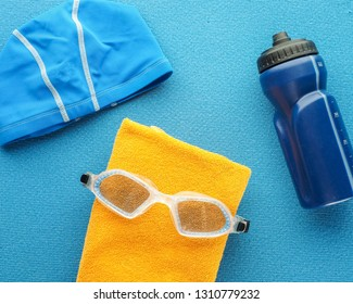 Flat lay composition with equipment for swimming pool  on blue background. Concept healthy lifestyle, sport and diet. Top view, text space.