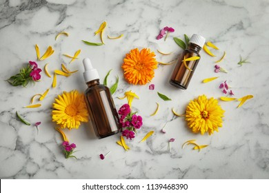 Flat lay composition with essential oils and flowers on marble background
