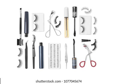 Flat lay composition with false eyelashes and cosmetic tools on white background