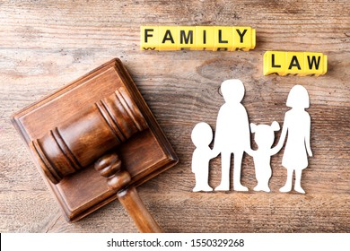 Flat lay composition with figure and gavel on wooden background. Family law concept