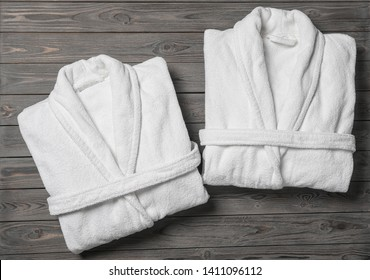Flat lay composition with folded bathrobes on wooden background