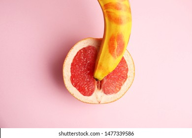 Flat lay composition with fresh banana  and grapefruit on pink background. Sex concept