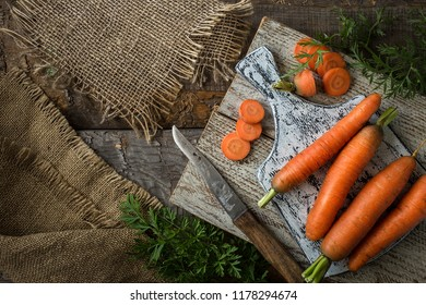 Flat lay composition with  fresh carrots on dark rustic  background.  Vegetables Vitamins Keratin. Natural organic healthy food concept. Top view