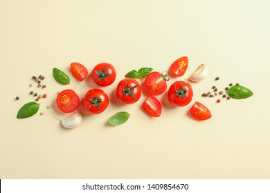 Flat lay composition with fresh cherry tomatoes, pepper, garlic and basil on color background, space for text. Ripe vegetables