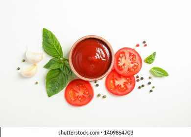 Flat lay composition with fresh cherry tomatoes slices, basil, pepper, garlic and sauce on white background, space for text. Ripe vegetables