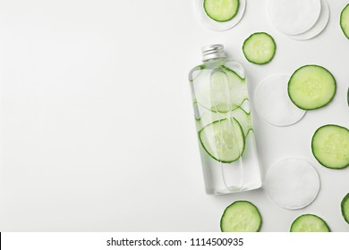 Flat lay composition with fresh cucumber skin care tonic and cotton pads on white background