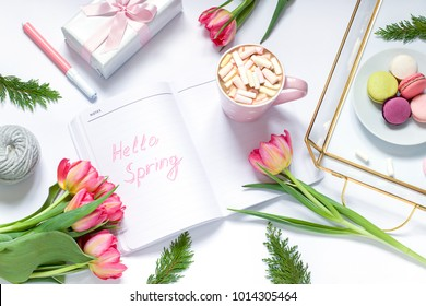 """Flat lay composition with fresh flowers, tray, coffee and macarons.  """"Hello spring"""" conceprt Top view. Copy space"""