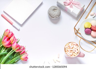 Flat lay composition with fresh flowers, tray, coffee and macaroons. Lifestyle concept frame. Top view. Copy space