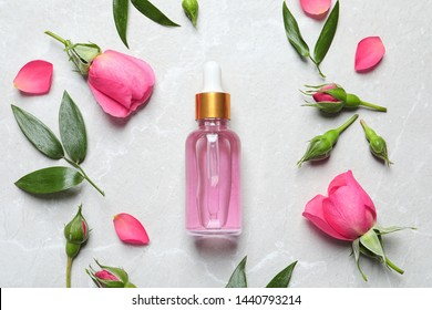 Flat lay composition with fresh flowers and bottle of rose essential oil on table