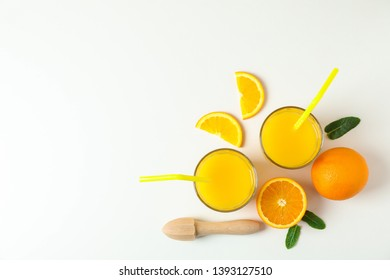 Flat lay composition with fresh orange juices, wooden juicer, mint, oranges and wooden juicer on white background, top view and space for text. Fresh natural drink and fruits