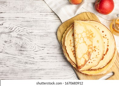 Flat lay composition with fresh thin pancakes on white wooden table table. Space for text