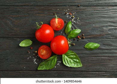 Flat lay composition with fresh tomatoes, salt, pepper and basil on wooden background, space for text. Ripe vegetables