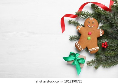 Flat lay composition with gingerbread man and Christmas decor on white wooden table, space for text