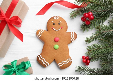 Flat lay composition with gingerbread man and Christmas decor on white wooden table