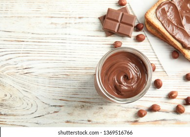 Flat lay composition with glass jar of tasty chocolate cream and hazelnuts on wooden background. Space for text