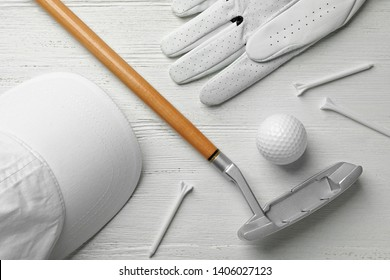 Flat lay composition with golf accessories on white wooden background
