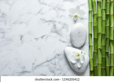 Flat lay composition with green bamboo stems on marble background. Space for text