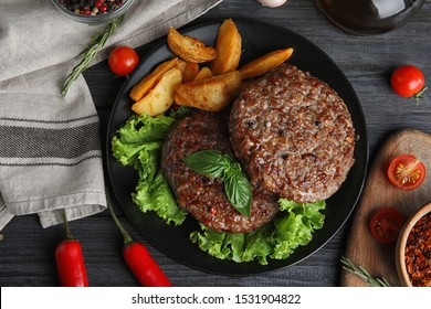 Flat lay composition with grilled meat cutlets for burger on black wooden table