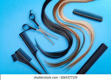 Flat lay composition with hairdresser's tools and strands of hair on color background