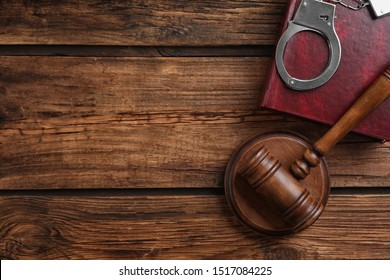 Flat lay composition with handcuffs and gavel on wooden table, space for text. Criminal law