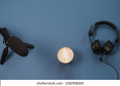Flat lay composition with Headphones, microphone and coffee on a blue background. Podcast or webinar concept.