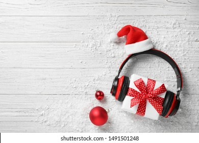 Flat lay composition with headphones on white wooden background, space for text. Christmas music concept