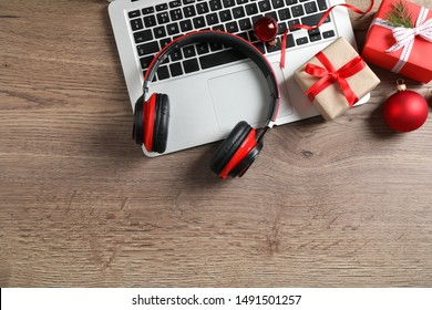 Flat lay composition with headphones on wooden background, space for text. Christmas music
