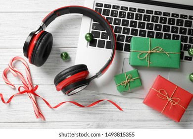 Flat lay composition with headphones on white wooden background. Christmas music