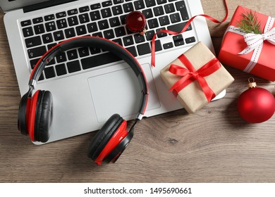Flat lay composition with headphones on wooden background. Christmas music