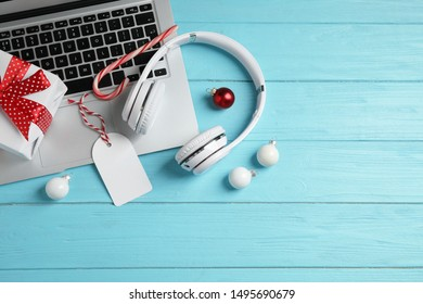 Flat lay composition with headphones on blue wooden background, space for text. Christmas music concept