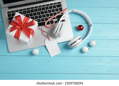 Flat lay composition with headphones on blue wooden background. Christmas music