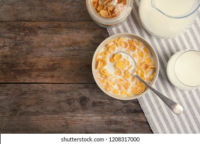 Flat lay composition with healthy cornflakes and milk in bowl on wooden table. Space for text